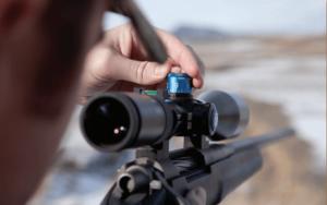 Man adjusting gun scope