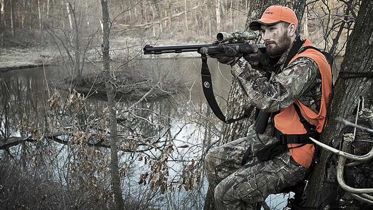 deer hunter aiming a black powder muzzleloader with a scope